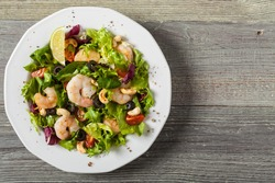 Shrimp salad with tomato, olives and cashew nuts. Top view
