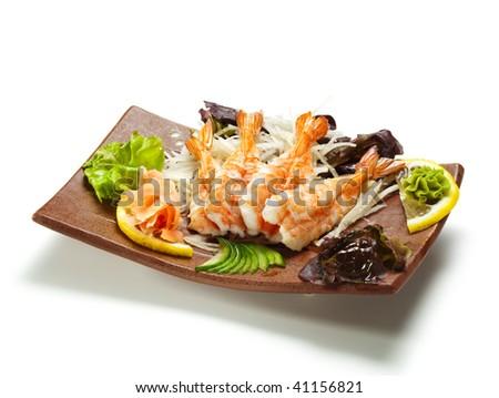 Shrimp Sashimi - Ebi (shrimp) on Daikon (White Radish). Garnished with Ginger, Wasabi, Seaweed, Cucumber, Salad Leaf and Lemon