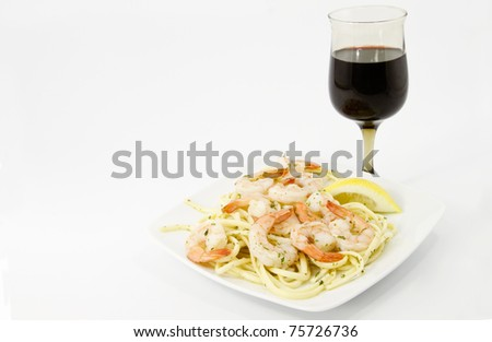 Shrimp scampi with herbs and lemon slice are served over olive tossed spaghetti with healthy red wine