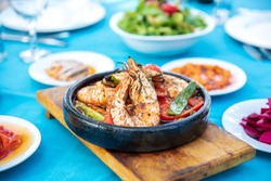 Shrimp, Seafoods, appetizers and salads on the table in Fish Restaurant. Beach Restaurant in Greece or Turkey. Aegean seaside, Greek or Turkish style fish restaurant in Bodrum, Santorini or Mykonos
