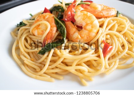 Shrimp spicy spaghetti thai style with herb on white dish close up picture.