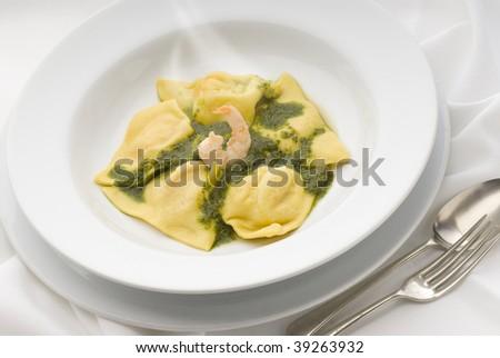 shrimp stuffed pasta with basil sauce - stock photo