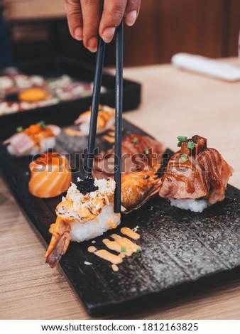 Shrimp sushi nigiri on a black plate with black chopsticks. Closeup of Japanese sushi set nigiri and sushi rolls.Eating japanese food on black slate dishes at restaurant