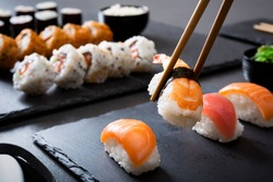 Shrimp sushi nigiri on a black plate with wooden chopsticks. Closeup of nigiri set with chopsticks and uramaki and hosomaki in background. Eating japanese food on black slate dishes at restaurant.