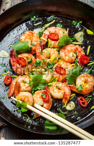 Shrimps and chopstick on pan with fresh herbs