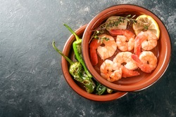 Shrimps and fried pimientos or padron peppers in stacked tapa bowls, traditional Spanish appetizer on a dark gray slate background, copy space, high angle view from above, selected focus