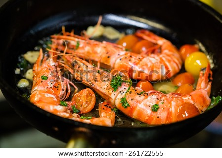 Shutterstock Shrimps on a cast iron skillet with cherry tomatoes in the restaurant. Process of cooking.
