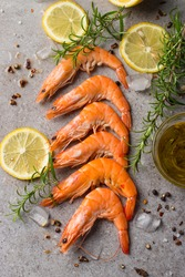 Shrimps on stone background. Grilled prawns with rosemary and lemon.