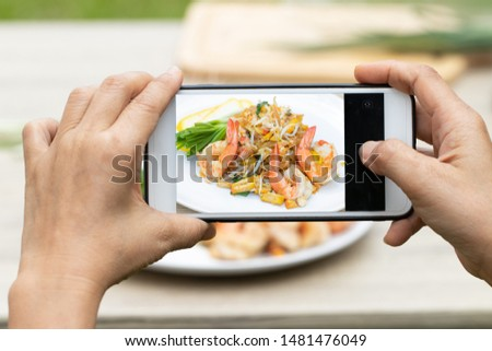 Shrimps Pad Thai or phad thai (Thailand's national dishes) on white dish with hand holding smart phone take photo