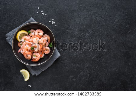 Shrimps, Prawns in bowl with lemon, sea salt and herbs, top view, copy space. Fresh seafood ingredient - shrimp tails on black. Boiled prawns.