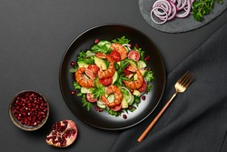 Shrimps salad with cherry tomatoes, cucumeber, avocado, lettuce and pomegranate on dish. Healthy seafood concept. Tasty grilled prawn shrimp and mix vegetable salad on black, top view.