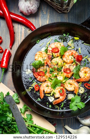 Shrimps served on a pan with chilli pepper