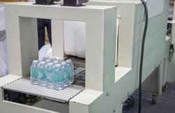 Shrink film wrapping machine for bottle of water. Food industry
