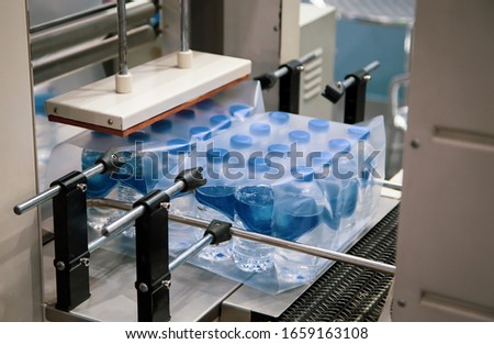 Shrink film wrapping machine for bottle of water. Food industry Сток-фото ©