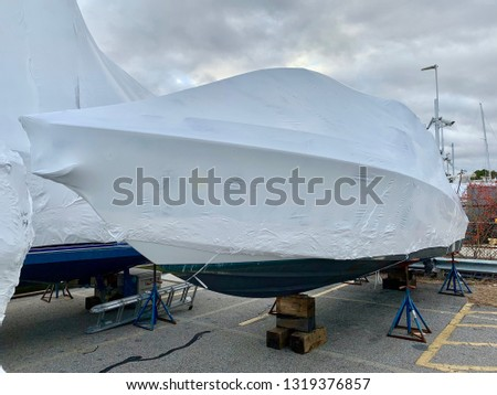 Shrink-wrapped boat on blocks for the winter