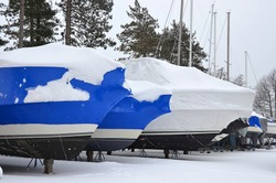 shrink wrapped boats covered with snow