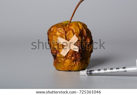 Shrivelled apple and insulin ultra thin syringe on a gray surface. Closeup