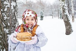 Shrovetide (Maslenitsa) Concept. Joyful little girl with pancakes on a plate in her hands and bagels around on her neck, Outdoor, Winter Time