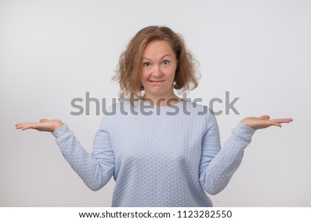 Shrugging norwegian woman wearing blue sweater in doubt doing shrug. Confused girl gesturing do not know sign on gray background