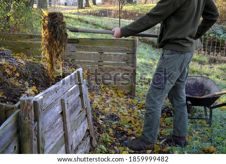 shuffling compost for aeration and better rot. the gardener uses a shovel and pitchfork in his hand. He has green pants and a jacket. Compost is in a wooden plank box. garden wheelbarrow Photo stock ©