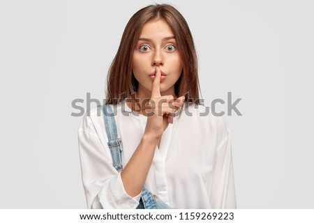 Shush, be silent! Serious lovely female asks to keep secret information confidential, dressed in white oversized shirt and denim overalls, poses against white studio wall. Conspiracy concept