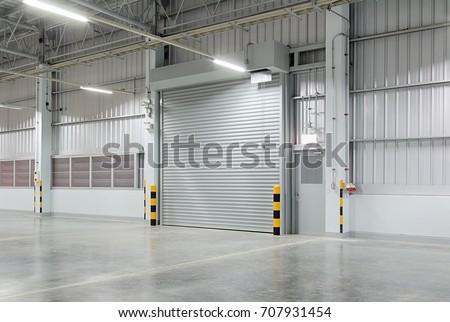 Shutter door or roller door and concrete floor inside factory building for industry background.