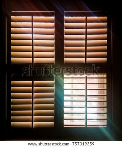 Shuttered window with one pane open letting through rays of light and a faint image of autumn leaves outside