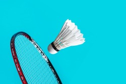Shuttle cock badminton and racket in the blue background.