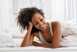 Shy black girl lying on bed under white blanket at home. Happy african american cute woman lying on front in bed in the morning. Beautiful young woman smiling while looking down on bed.