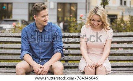 Photo of  Shy blonde girl smiling, attractive guy flirting with beautiful woman on bench