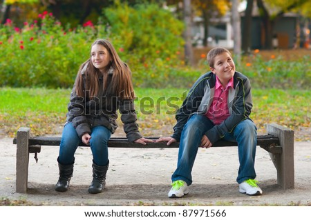 Shy boy and the girl sitting in the park and lightly touching each other finger tips.