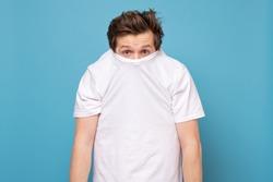 Shy caucasian man hiding behind his white shirt being afraid of coronavirus. Studio shot on blue wall.