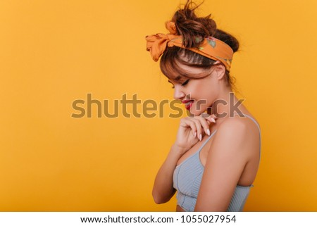 Shy cute woman with retro outfit posing with smile on yellow background. Trendy amazing lady wears tank-top and hair accessory standing in studio.