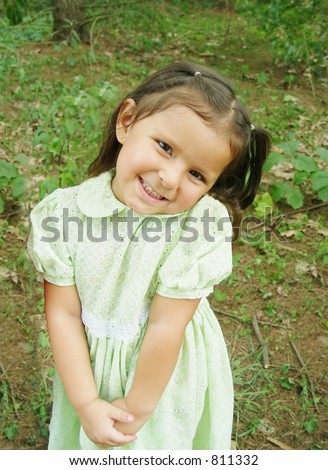 Shy little Native American girl in swiss-dot eyelet patterned green dress.