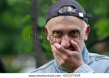 0589715d8da Shy man wearing backward cap about to laugh