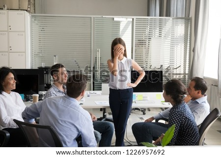 Shy nervous bashful female employee feels embarrassed blushing afraid of public speaking at corporate group team meeting, timid stressed woman hiding face during awkward moment reporting in office