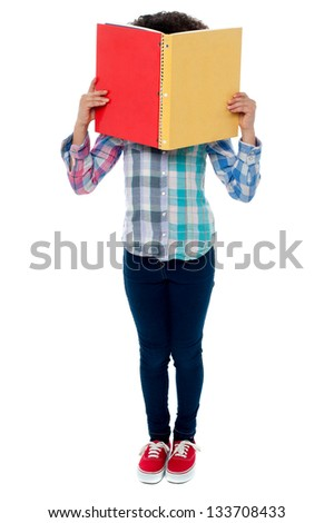 Shy school girl hiding her face behind colored notebook.