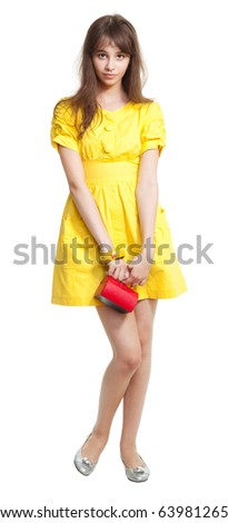 Shy teenage girl in yellow with small vivid red purse