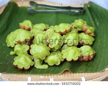 Siam Pandan Thai dessert or Kanom Krok Singapore or Kanom Krok Bai Toey : traditional Thai pancake made from flour, egg, sugar and pandan flavour in flower shaped pan Zdjęcia stock ©