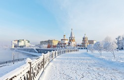Siberian city of Irkutsk on frosty winter day. View from the snow-covered lower embankment of the Angara River to the Epiphany Cathedral and the monument to the founders of the city. Winter cityscape