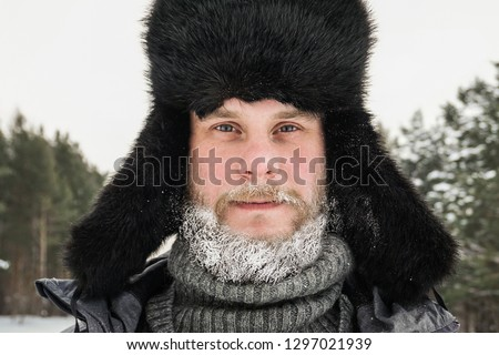 Siberian Russian man with a beard in hoarfrost in freezing cold in the winter freezes in a village in a snowdrift and wears a hat with a earflap. #1297021939