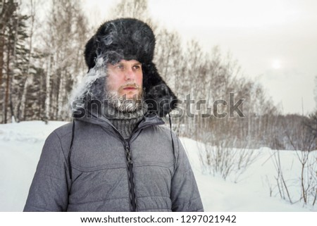 Siberian Russian man with a beard in hoarfrost in freezing cold in the winter freezes in a village in a snowdrift and wears a hat with a earflap. #1297021942