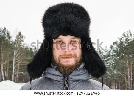 Siberian Russian man with a beard in hoarfrost in freezing cold in the winter freezes in a village in a snowdrift and wears a hat with a earflap. #1297021945