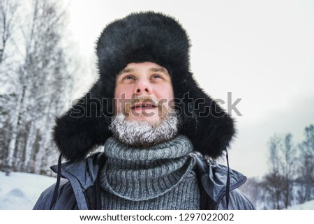 Siberian Russian man with a beard in hoarfrost in freezing cold in the winter freezes in a village in a snowdrift and wears a hat with a earflap. #1297022002