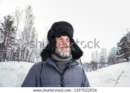 Siberian Russian man with a beard in hoarfrost in freezing cold in the winter freezes in a village in a snowdrift and wears a hat with a earflap smoking a cigarette #1297022056