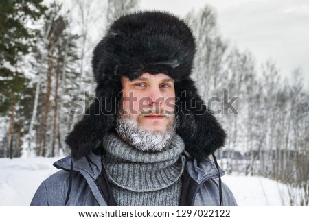Siberian Russian man with a beard in hoarfrost in freezing cold in the winter freezes in a village in a snowdrift and wears a hat with a earflap. #1297022122