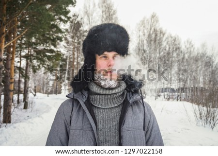 Siberian Russian man with a beard in hoarfrost in freezing cold in the winter freezes in a village in a snowdrift and wears a hat with a earflap. #1297022158
