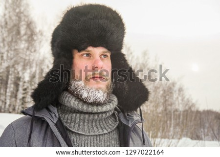 Siberian Russian man with a beard in hoarfrost in freezing cold in the winter freezes in a village in a snowdrift and wears a hat with a earflap. #1297022164