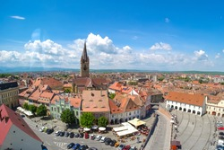 Sibiu, Transylvania, Romania. Panoramic view of the Small Square (Piata Mica) with the old Catholic Cathedral and the Liars Bridge visible in the back. Important tourist attraction.