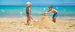 Sibling boy building a sandcastle at the beach in summer